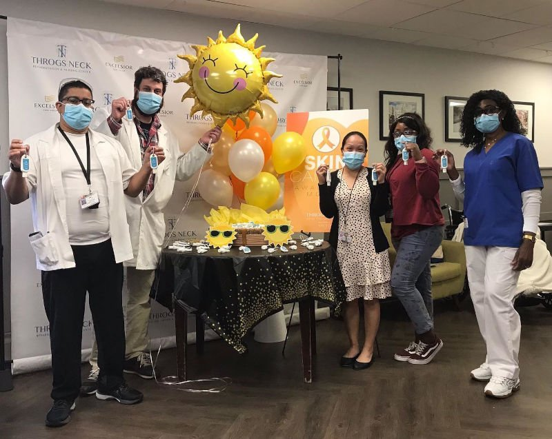 Group of employees standing around table with sunshine balloon